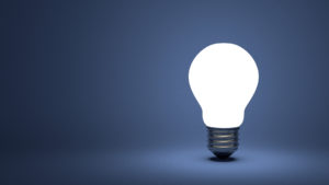 Glowing light bulb on blue